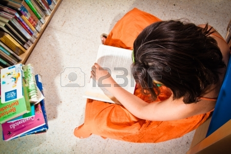 13897781-a-little-girl-reading-in-a-library-sitting-on-the-floor-completely-absorbed-in-her-book-seen-from-ab